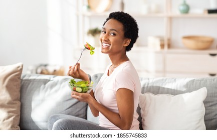 Healthy nutrition concept. Pretty black woman eating yummy vegetable salad on sofa at home, panorama. Slim African American lady maintaining weight by balanced vegan meal