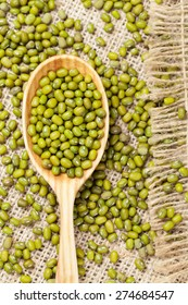 Healthy nutrition green raw organic mung beans in wooden spoon on vintage textile background