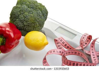 Healthy nutrition. Scales, measuring tape and vegetables on a white background.  Healthy lifestyle concept. Slimming, diet, and control of weight.