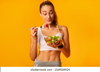 Healthy Nutrition. Sporty Woman Eating Vegetable Salad Holding Bowl Standing Over Yellow Background. Studio Shot