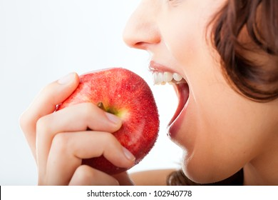 Healthy nutrition and healthy teeth or diet, young woman bites in a apple