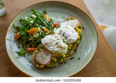 Healthy nutritious breakfast idea: avocado toast topped with corn, radish and poached eggs with salad at a side. Plant-based concept for food. Selective focus.