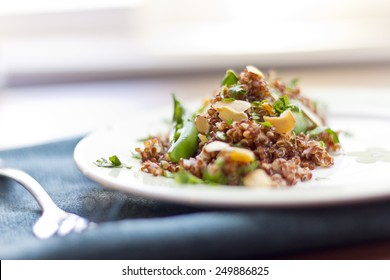 Healthy nutty red quinoa salad with sugar snap peas sliced toasted almonds and chopped parsley