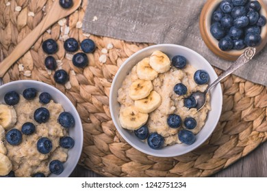 Healthy oatmeal porridge breakfast with fresh blueberries and sliced bananas. There are two bowls in the photo, one partly out of the frame, and two vintage spoons.