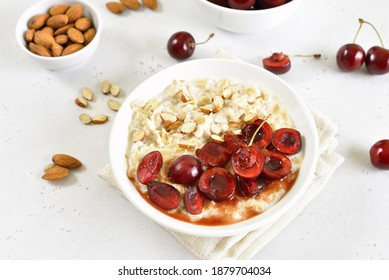 Healthy oatmeal porridge with cherry slices and nuts in bowl