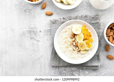 Healthy oats porridge with banana slices, almond and dried apricot on stone background with copy space. Healthy diet food. Top view, flat lay