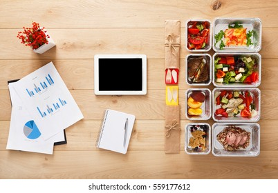 Healthy office lunch. Restaurant food for diet. Fresh daily meals delivery. Fitness nutrition, vegetable, meat and fruits in foil boxes, coffee and tablet. Top view, flat lay on wood with copy space