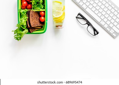 Healthy office snacks. Lunch box with cherry tomatoes, salad, bread near keyboard on white background top view copyspace