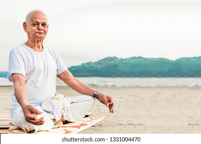 Healthy Old Indian Man, Super Senior Citizen performing Yoga, sitting in Lotus Pose and doing meditation on beach. He is wearing dhoti, has pretty wrinkles on his face and is happily posing for camera