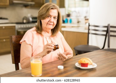 Healthy old Latin lady taking her daily vitamins while eating breakfast at home