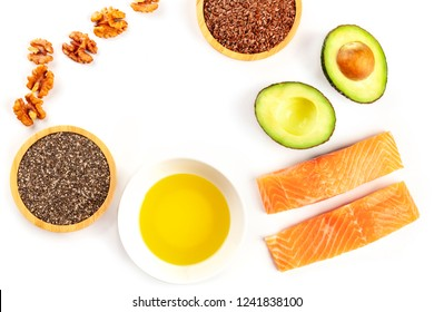 Healthy omega-3 diet food ingredients. Raw salmon, avocado, nuts, chia seeds, flaxseeds, shot from above on a white background, forming a frame for copy space