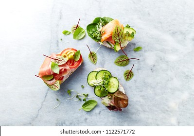 Healthy open sandwiches with vegetables, herbs, salmon, ham, herbs and soft cheese. Flat lay. Healthy diet concept.