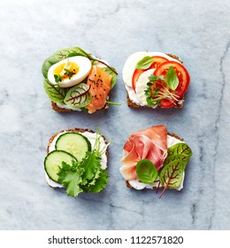 Healthy open sandwiches with vegetables, salmon, ham, herbs and soft cheese. Flat lay. Healthy diet concept.