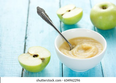 Healthy organic applesauce (apple puree, mousse, baby food, sauce) in white bowl on table with green apples