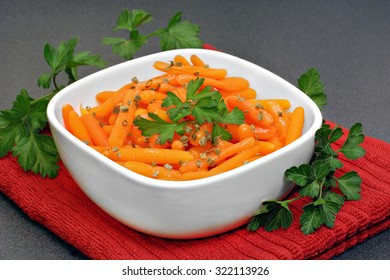 Healthy, organic baby carrots in a bowl garnished with parsley.