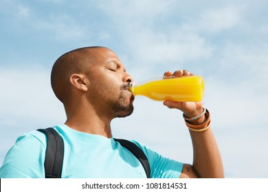Healthy organic drinks. Portrait of dark skinned guy drinking tasty fresh orange juice. African man sitting on warm summer evening against blurred background of beautiful nature