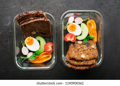 A healthy organic farm breakfast. Slices of cereal bread, cucumber, boiled egg, radish, berries, nuts, fruits, greens for a useful lunch lunch fitness lunch in trendy glass containers. Top View