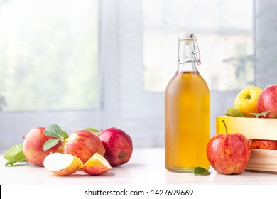 Healthy organic food. Apple cider vinegar in glass bottle and fresh red apples on a light background.