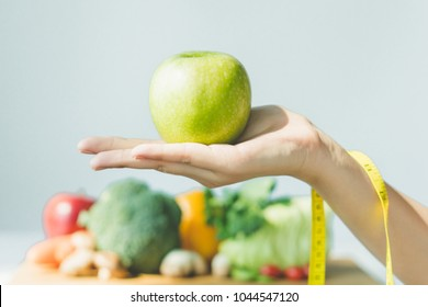 Healthy organic food for dieting woman concept. Woman carry green apple in front of healthy food and having a measure on her arm.
