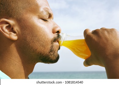 Healthy organic food. Portrait of dark skinned guy drinking tasty fresh orange juice. African man sitting on warm summer evening against blurred background of beautiful nature