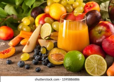 Healthy organic fresh multivitamin fruit juice with seasonal fruit decoration on rustic wooden table