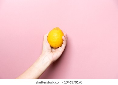 Healthy organic lemon in a woman hand. Pink background.