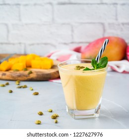 Healthy organic mango lassi, smoothie, shake, indian drink beverage with yogurt and fresh ripe fruits on a kitchen table.