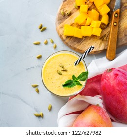 Healthy organic mango lassi, smoothie, shake, indian drink beverage with yogurt and fresh ripe fruits on a kitchen table. Top view flat lay background