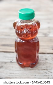 Healthy organic natural sweetener, raw honey - from bees. Golden brown liquid in bear shaped bottle with green cap. Isolated on solid wooden background with blank empty room space for text or copy.