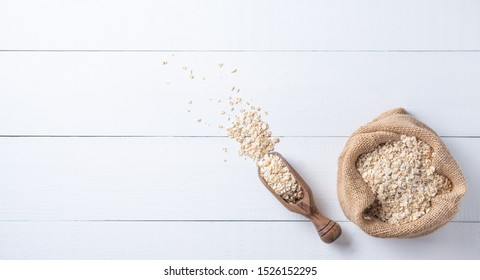 Healthy and organic oat flakes in sack with wood spoon on the white wooden table. Vegan food. Image is copy space, gorizontal orientation and top view