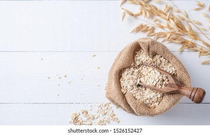 Healthy and organic oat flakes in sack with wood spoon and branch on the white wooden table. Vegan food. Image is copy space, macro,close up and top view