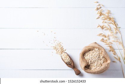Healthy and organic oat flakes in sack with wood spoon and branch on the white wooden table. Vegan food. Image is copy space and top view