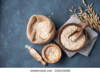 Healthy and organic oat flakes in wood bowls and sack with  spoon and branch on the gray napkin and  dark blue wooden table. Vegan food. Image is copy space and top view