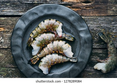 Healthy organic tiger shrimps in a plate on a wooden table top view