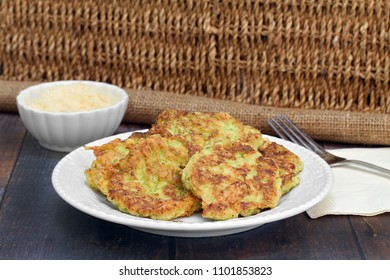 Healthy, organic zucchini fritters on a white plate in a rustic setting of wicker and burlap.