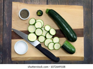 Healthy organic zucchini on a cutting board.  Both whole and sliced squash.  Top view.
