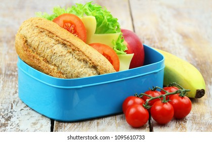 Healthy packed lunch box containing brown cheese roll, apple, banana and cherry tomatoes