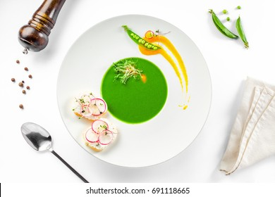 Healthy pea cream soup in a rim soup plate. Delicious European cuisine meal isolated on white background.