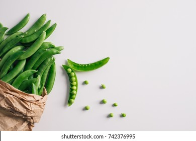Healthy pea in paper shopping bag. Top view on white table top with copy space.