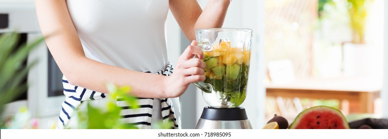 Healthy person standing in the kitchen preparing a fruit cocktail containing kiwi pineapple and water in a blender