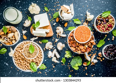 Healthy plant vegan food, veggie protein sources: Tofu, vegan milk, beans, lentils, nuts, soy milk, spinach and seeds. Dark blue concrete background copy space