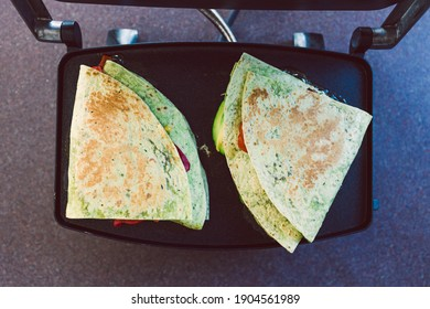 healthy plant-based food recipes concept, vegan version fo the viral layered tortilla wrap hack with red peppers grated dairy-free cheese avocado and refried beans on sandwich press grill