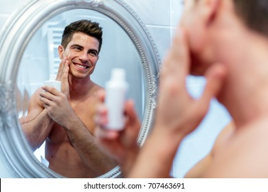 Healthy positive male treating sking with lotion