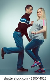Healthy pregnancy concept. Funny full length portrait of happy husband and pregnant wife making useful exercises in trendy sportswear together. Hipster style. Studio shot