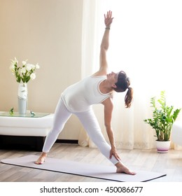 Healthy Pregnancy Yoga and Fitness concept. Young pregnant yoga woman working out in cozy living room interior. Pregnant model doing prenatal Extended triangle, Utthita Trikonasana yoga pose