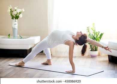 Healthy Pregnancy Yoga and Fitness concept. Young pregnant yoga woman working out in living room. Pregnant model doing prenatal Camatkarasana, Wild Thing or Flip-the-Dog posture yoga backbend exercise