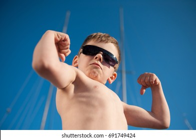 healthy preschool child in black sunglasses showing his biceps