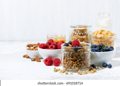 healthy products for breakfast, granola and fresh berries on white table, horizontal