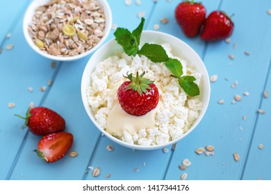 Healthy proper wholesome food. Fresh tasty granular cottage cheese with strawberries in a white deep plate on a blue wooden background, dry muesli and berries of fresh strawberries are scattered aroun