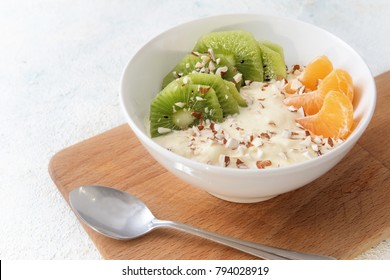 healthy protein breakfast, quark curd cheese, linseed oil with omega 3, fresh fruits and nuts, budwig diet in a white bowl on a wooden kitchen board and a light background, copy space, selected focus
